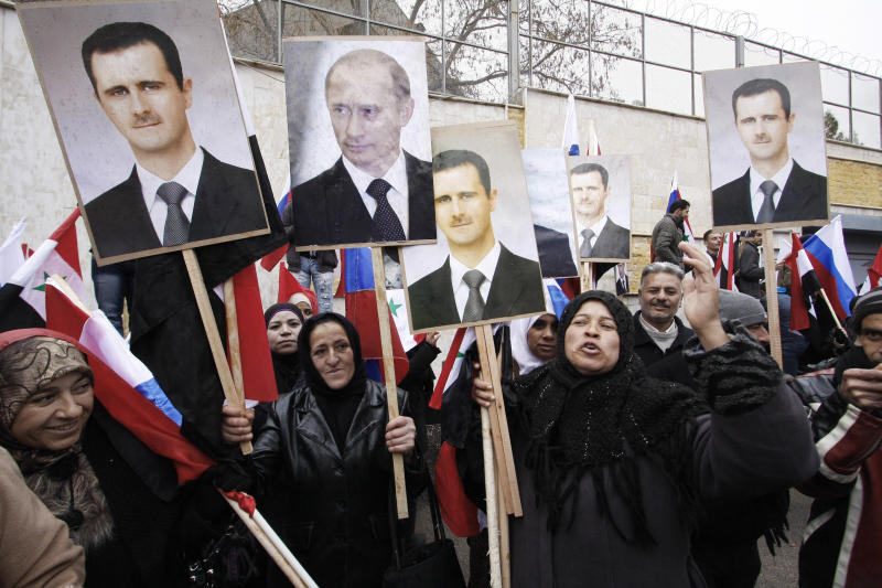 FILE - In this Sunday, March 4, 2012 file photo, Syrians hold photos of Syrian President Bashar Assad and Russian Prime Minister Vladimir Putin during a pro-Syrian regime protest in front of the Russian embassy in Damascus, Syria. In a few days' worth of opportunistic diplomacy, Vladimir Putin has revived memories of an era many thought long gone, where the United States and Soviet Union jostled for influence in a Middle East torn between two powers. Whatever happens with its proposal to relieve Syria of chemical weapons, Russia reemerges as a player in the region _ and one who does not easily abandon allies. That's meaningful in a region where America's dumping of Hosni Mubarak has emerged as a seminal moment _ and it may resonate with Iran, whose leaders are carefully watching the global chessboard as the clock ticks toward another showdown, over their nuclear program. (AP Photo/Muzaffar Salman, File)
