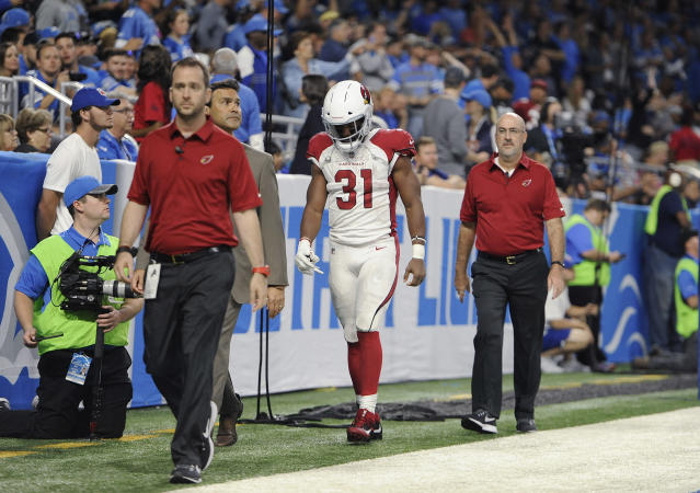 Cardinals RB David Johnson leaves the field with team medical staff on Sunday after injuring his wrist. (AP)