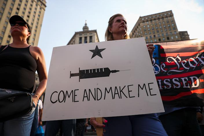 Protesters stand against a backdrop of skyscrapers holding signs, one of which shows an image of a hypodermic needle and reads: Come and make me.