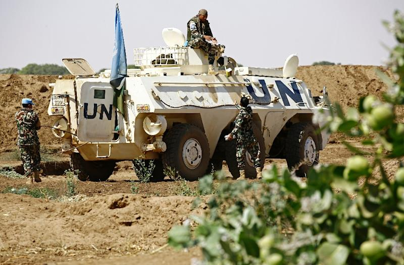 United Nation peacekeepers rest next to an armoured personnel carrier about 60 kilometres north of El-Fasher, the capital of the North Darfur state, on February 9, 2017