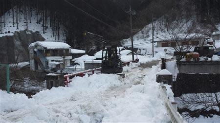A Japan Ground Self-Defense Force excavator removes snow covering a bridge at Hinohara village
