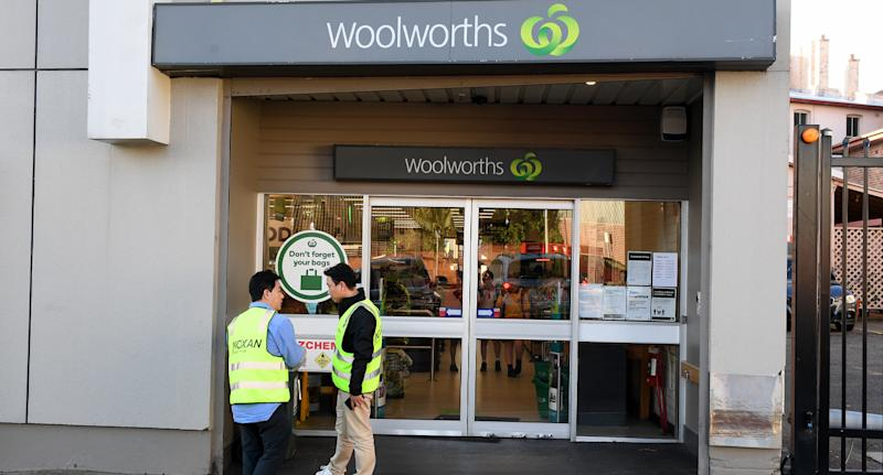 Photo shows front of Woolworths store with two people in high-vis out front.