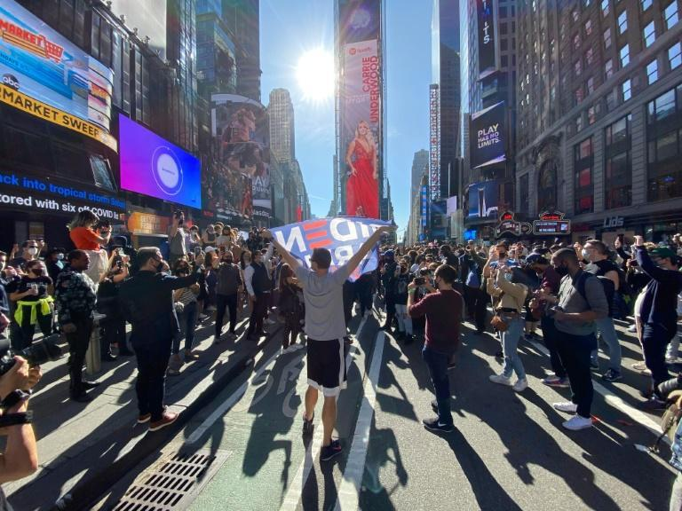 People celebrate at Times Square in New York after Joe Biden was declared winner of the 2020 presidential election on November 7, 2020