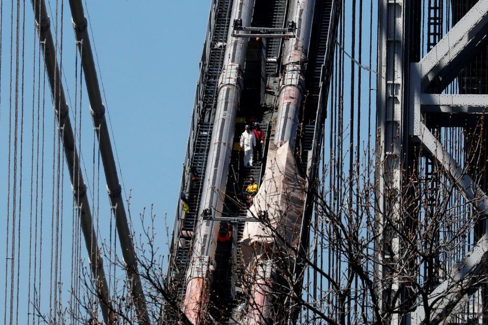 Construction workers are pictured on the northeast cables of the George Washington Bridge, which is undergoing a multi-year reconstruction in New York City, New York, U.S., March 30, 2021. REUTERS/Mike Segar