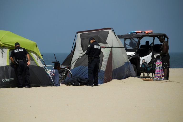 Los Angeles police inspect an encampment at Venice Beach on June 16, 2021 where Rodrick Mims, 50, (R) who has been homeless off and on over the last 15 years, is living by the Pacific Ocean