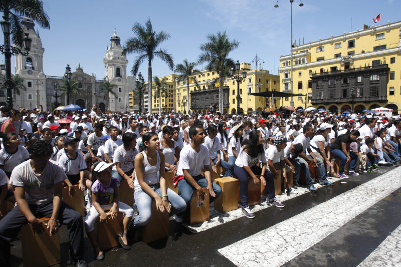 FILE - This April 14, 2012 file photo shows participants playing their cajons, a box-shaped percussion instrument of Afro-Peruvian origin, in hopes of beating their country's 2009 Guinness World Record for the world's largest cajon ensemble during the Fifth International Festival of the Peruvian Cajon at the Plaza de Armas in Lima, Peru. (AP Photo/Karel Navarro, file)