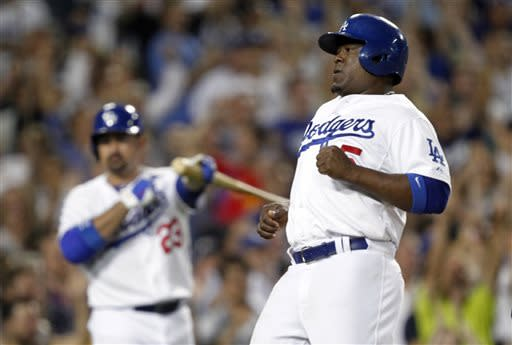 Los Angeles Dodgers' Juan Uribe (5) scores with Dodgers' Adrian Gonzalez, left, directing traffic in the eighth inning against the Philadelphia Phillies during a baseball game Thursday, June 27, 2013, in Los Angeles. Dodgers score two runs on a single by Dodgers' Yasiel Puig. (AP Photo/Alex Gallardo)