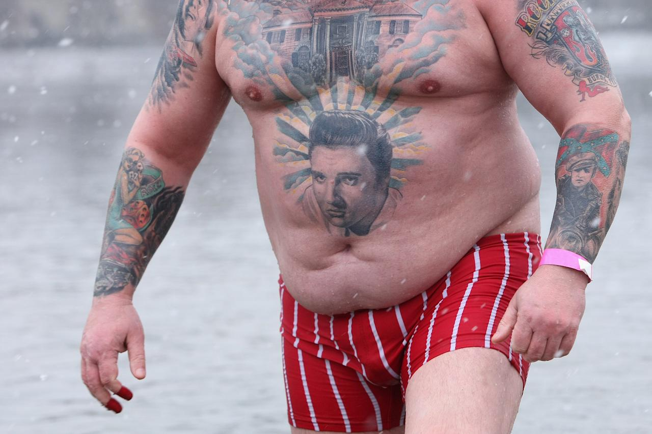 BERLIN, GERMANY - JANUARY 12:  An ice swimming enthusiast with a tattoo of Elvis wades in the cold waters of Orankesee lake during the 'Winter Swimming in Berlin' event on January 12, 2013 in Berlin, Germany. A local swimmers' group called the 'Berlin Seals' invite ice swimmers from across Germany and abroad to the annual event, which, despite warmer temperatures this winter and a lack of ice, was still held. Members claim ice swimming is good for the body's blood circulation.  (Photo by Adam Berry/Getty Images)