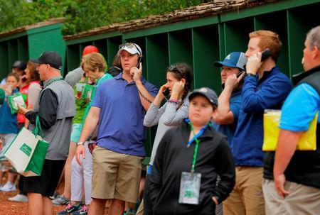 FILE PHOTO: Patrons use landline phones to call out as cell phones are not allowed on the course during Monday practice rounds for the 2017 Masters at Augusta National Golf Course in Augusta, Georgia, U.S., April 3, 2017. REUTERS/Jonathan Ernst/File Photo