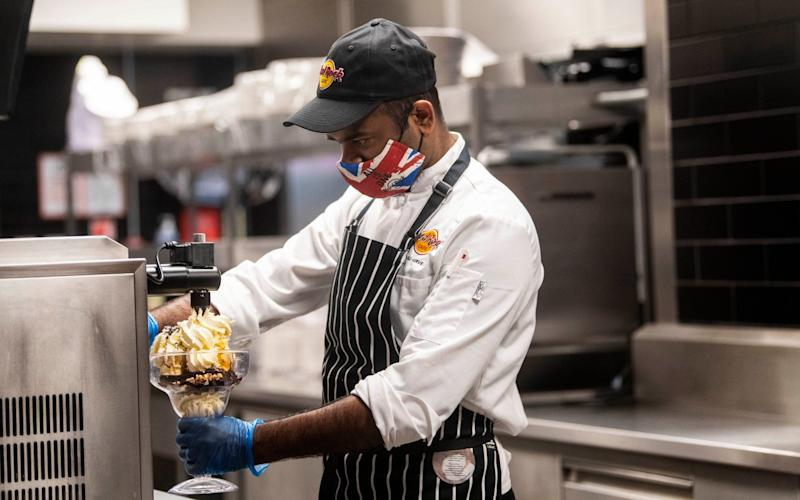 A chef wears PPE as he makes a chocolate brownie in the kitchen of the Hard Rock Cafe's European flagship restaurant in Piccadilly Circus, London - Victoria Jones/PA