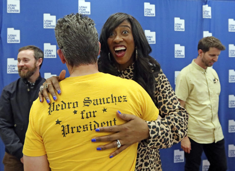 """In this May 3, 2019, photo, Shondrella Avery, who played the character LaFawnduh, hugs a fan wearing a Pedro shirt during a photo-op as they celebrate the 15th anniversary of """"Napoleon Dynamite,"""" in Salt Lake City. (AP Photo/Rick Bowmer)"""