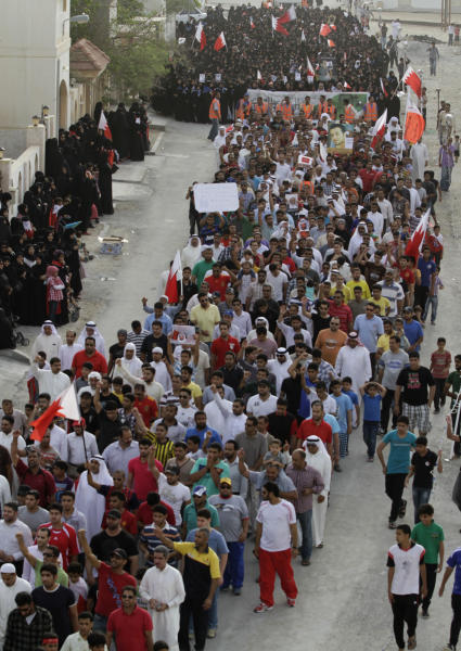 Bahraini anti-government protesters wave national flags during a march Tuesday, April 17, 2012, in Al-Dair, Bahrain, chanting anti-government slogans and carrying banners urging freedom for political prisoners. Some protesters carried signs against next Sunday's Formula One Bahrain Grand Prix, which has been the target of boycott calls. (AP Photo/Hasan Jamali)