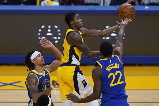 Indiana Pacers guard Edmond Sumner, top, shoots between Golden State Warriors guard Damion Lee, left, and forward Andrew Wiggins (22) during the first half of an NBA basketball game in San Francisco, Tuesday, Jan. 12, 2021. (AP Photo/Jeff Chiu)