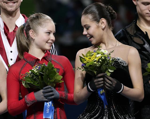 Elena Ilinykh, right, speaks with Julia Lipnitskaia as they stand on the podium during the flower ceremony after Russia placed first in the team figure skating competition at the Iceberg Skating Palace during the 2014 Winter Olympics, Sunday, Feb. 9, 2014, in Sochi, Russia