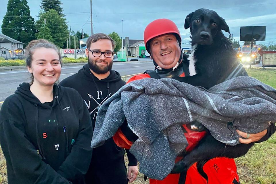 fireman holding black dog he rescue, standing with the couple that discovered the dog