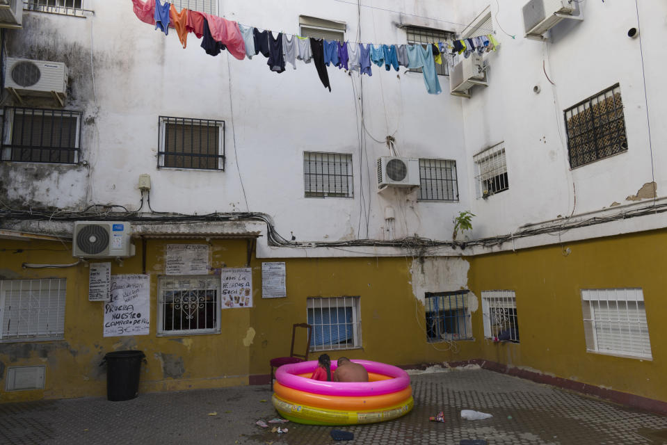 "Two people sit in a plastic pool in Seville, Spain on Aug. 19, 2020. Isabel says that ""it is terrible as we have to live but my son has Down syndrome and he has a Covid 10 risk profile so we can't go to the public pool"". (AP Photo/Laura Leon)"