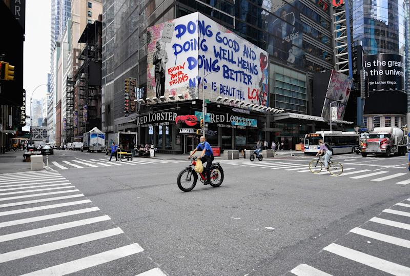 """A person rides his bike near Time Square on Sept. 28, 2020 in New York City. Coronavirus infection rates have increased at """"an alarming rate"""" in several New York neighborhoods, particularly among the Orthodox Jewish community in Brooklyn, city health authorities warned Sunday, threatening to sanction certain schools if they fail to comply with anti-virus regulations."""