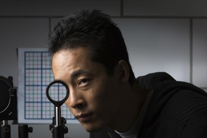 University of Rochester Ph.D. student Joseph Choi demonstrates a cloaking device using four lenses in Rochester, New York in this September 11, 2014 University of Rochester handout photo. Scientists at the University of Rochester have discovered a way to hide large objects from sight using inexpensive and readily available lenses, a technology that seems to have sprung from the pages of J.K. Rowling's Harry Potter fantasy series. Picture taken September 11, 2014. REUTERS/J. Adam Fenster/University of Rochester/Handout via Reuters (UNITED STATES - Tags: SCIENCE TECHNOLOGY EDUCATION SOCIETY TPX IMAGES OF THE DAY) ATTENTION EDITORS - THIS PICTURE WAS PROVIDED BY A THIRD PARTY. REUTERS IS UNABLE TO INDEPENDENTLY VERIFY THE AUTHENTICITY, CONTENT, LOCATION OR DATE OF THIS IMAGE. FOR EDITORIAL USE ONLY. NOT FOR SALE FOR MARKETING OR ADVERTISING CAMPAIGNS. THIS PICTURE IS DISTRIBUTED EXACTLY AS RECEIVED BY REUTERS, AS A SERVICE TO CLIENTS. NO SALES. NO ARCHIVES