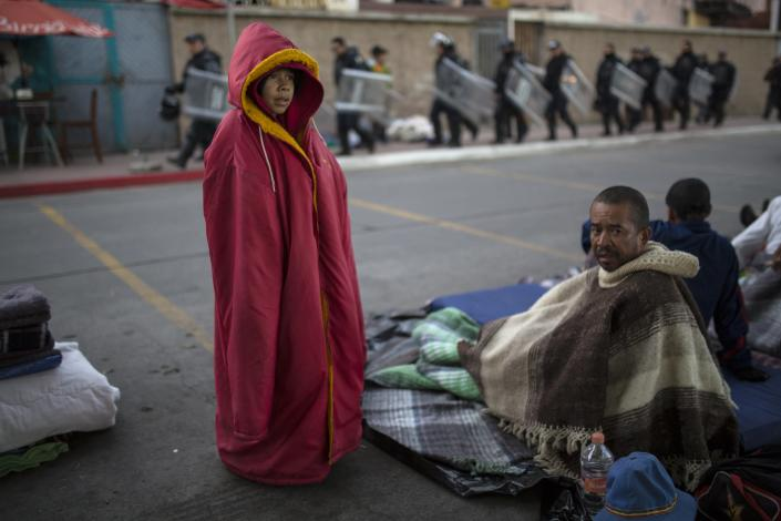 Jonathan Torres, 11, stands next to his father after waking up early in the morning as Mexican riot police make their way to the Chaparral border crossing, in Tijuana, Mexico, Friday, Nov. 23, 2018. The mayor of Tijuana has declared a humanitarian crisis in his border city and says that he has asked the United Nations for aid to deal with the approximately 5,000 Central American migrants who have arrived in the city.(AP Photo/Rodrigo Abd)