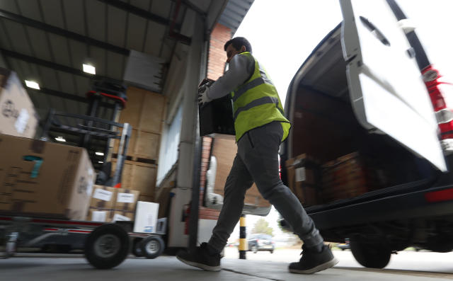 Lovespace warehouse worker Pawel Mazur unloads boxes at the warehouse in Dunstable, England Monday, Jan. 14, 2019. Lovespace, which collects boxes from customers, stores them and then returns the goods when needed, says revenue from businesses doubled over the past year as enterprises large and small began stockpiling inventory because of concerns they will be cut off from suppliers if Britain leaves the European Union without an agreement on future trading relations. (AP Photo/Alastair Grant)