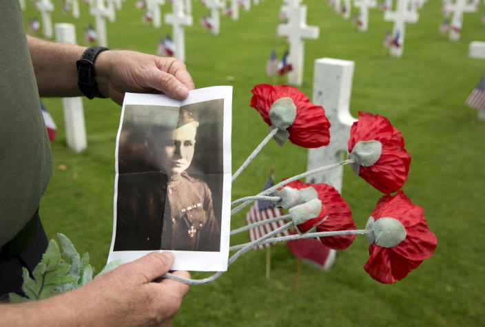<p>Mark Shively, from Beaverton, Oregon, shows a photo of his grandfather, World War I Marine Corps Private Norman Alfred Roberts, as he leaves flowers at the grave of his grandfather's unit commander Lt. Carleton Burr during Memorial Day weekend at the Aisne-Marne American Cemetery in Belleau, France, Saturday, May 26, 2018. Roberts, wounded during the Battle of Belleau Wood in June of 1918, made it home to America before the war ended. His unit commander Lt. Carleton Burr was killed in nearby Vierzy, France in July 1918. (Photo: Virginia Mayo/AP) </p>