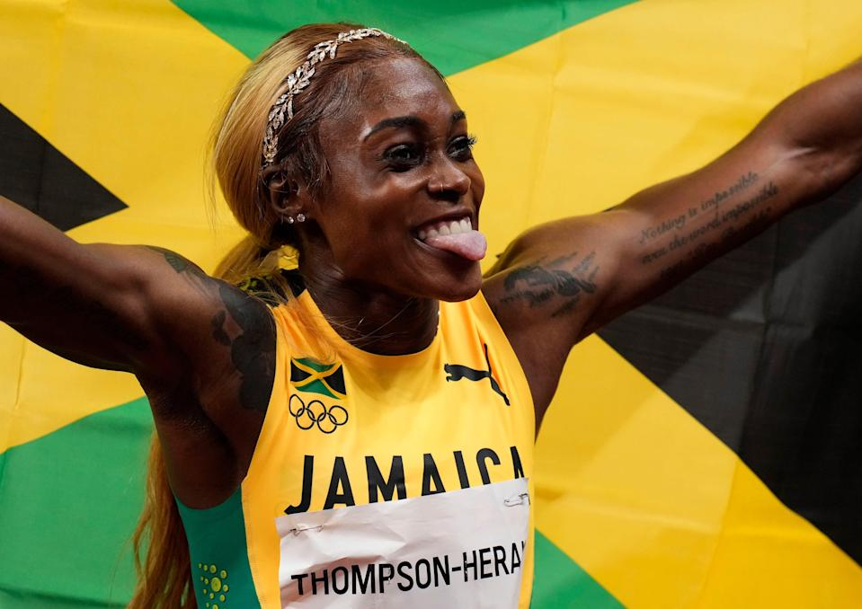 Elaine Thompson-Herah celebrates after winning the women's 100 final during the Tokyo 2020 Summer Olympic Games at Olympic Stadium.