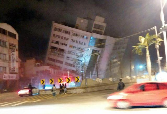 <p>In this photo released by Hualien County Fire Bureau, rescuers are seen entering an building that collapsed onto its side from an early morning earthquake in Hualien County, eastern Taiwan, Feb. 7, 2018. (Photo: Hualien County Fire Bureau via AP) </p>
