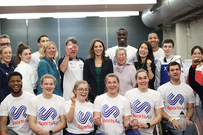 The Duchess of Cambridge (centre) poses for a photograph with young athletes and staff during a SportsAid event at the London Stadium in Stratford, London.