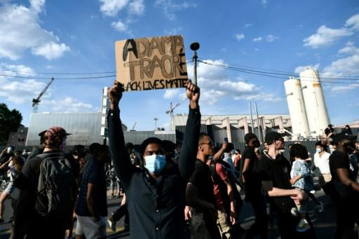 Some 20,000 people protest the 2016 death of a young black man named Adama Traore in French police custody, using slogans echoing those in the demonstrations raging in the US