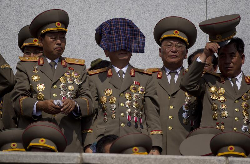 A North Korean military veteran uses a handkerchief to protect himself from the sun in the stands at a mass military parade on Kim Il Sung Square in Pyongyang to mark the 60th anniversary of the Korean War armistice in North Korea, Saturday, July 27, 2013. (AP Photo/David Guttenfelder)