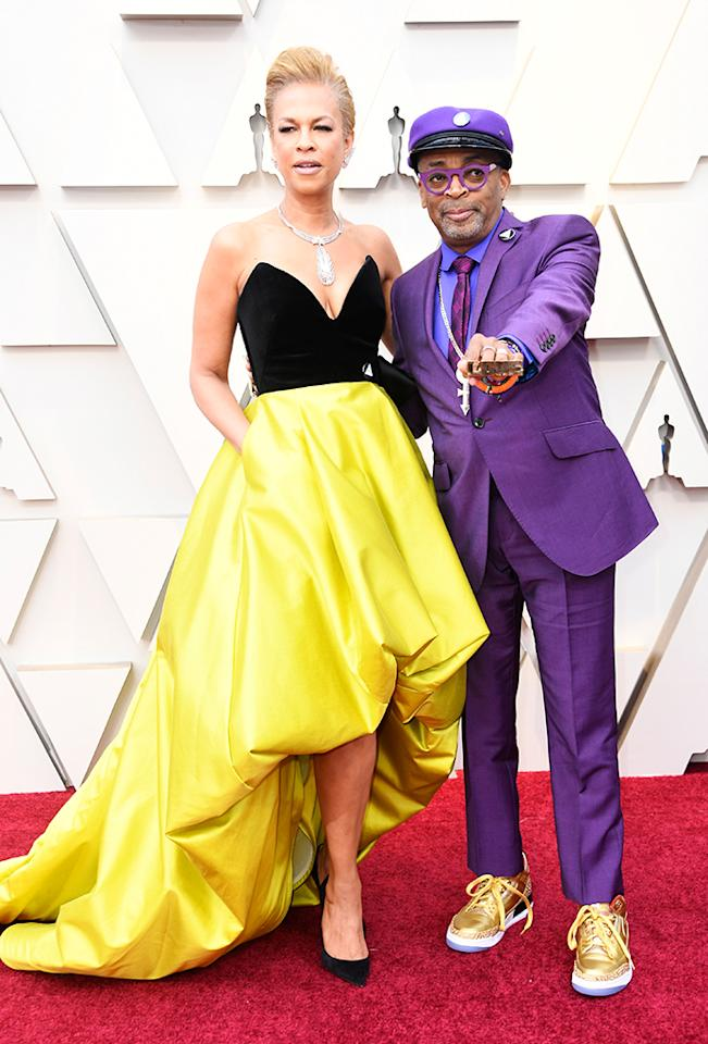 """<p><i>BlacKkKlansman</i> helmer Spike Lee, a nominee for directing, hit the carpet with his wife, Tonya Lewis Lee, in a purple suit, as a tribute to Prince. He accessorized with a necklace of Prince's love symbol, as well as knuckle rings that made a statement, reading """"love"""" and """"hate."""" (Photo: Getty Images) </p>"""
