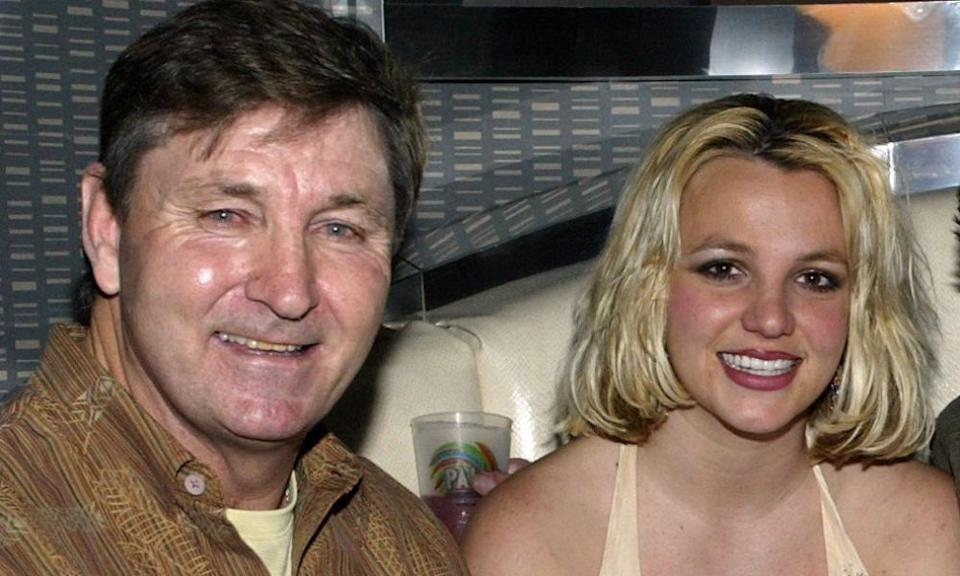 Jamie Spears in a brown jacket and Britney Spears in a vest smile at the camera