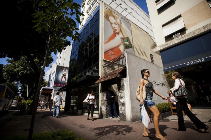 """Pedestrians walk past giant billboards advertising clothing in Rio de Janeiro, Brazil, Wednesday, May 2, 2012. Billboards on beachfront buildings, advertising along roadways and soccer fields, will now be torn down under the """"Clean Rio"""" campaign, meant to beautify the town before the 2014 World Cup and 2016 Olympics. (AP Photo/Victor R. Caivano)"""