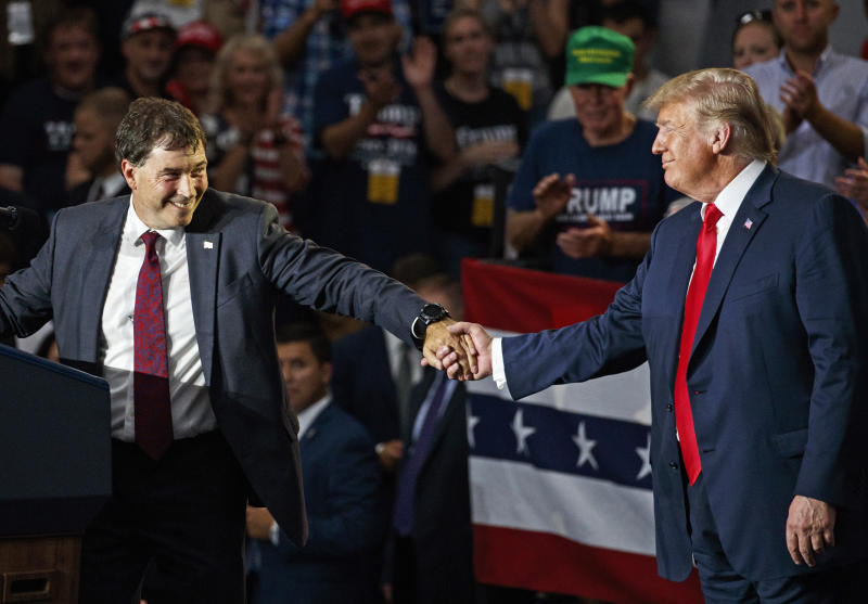 FILE – In this Aug. 4, 2018, file photo, Ohio state Sen. Troy Balderson, left, the Republican candidate running to succeed former Republican U.S. Rep. Pat Tiberi in Ohio's 12th District, clasps hands with President Donald Trump as Balderson speaks during a rally at Olentangy Orange High School in Lewis Center, Ohio. Balderson, a two-term state senator backed by Trump but who also promoted his ties to Trump critic Ohio Gov. John Kasich, has won a previously deadlocked congressional special election in Ohio, retaining a coveted open U.S. House seat long held by Republicans. (AP Photo/Carolyn Kaster, File)