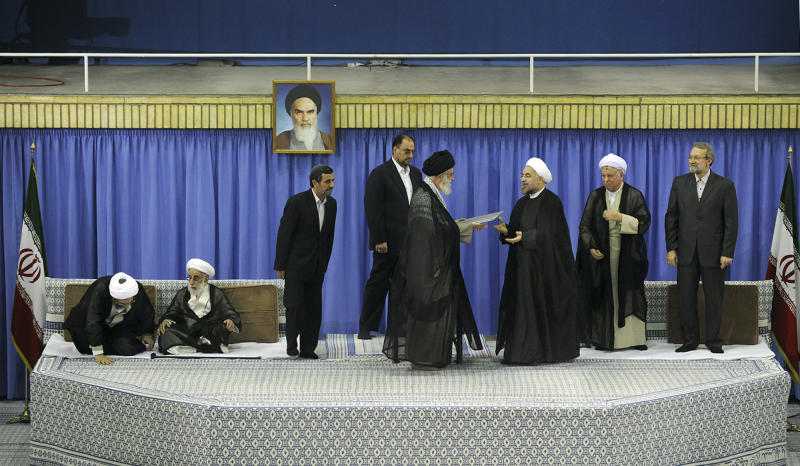 In this picture released by the official website of the Iranian supreme leader's office, Supreme Leader Ayatollah Ali Khamenei, center with black turban, gives his official seal of approval to President-elect Hasan Rouhani, in an official endorsement ceremony, in Tehran, Iran, Saturday, Aug. 3, 2013. Iran's supreme leader has formally endorsed Hasan Rouhani as president opening the way for the moderate cleric to take over from outgoing President Mahmoud Ahmadinejad. Parliament speaker Ali Larijani, right, head of the Expediency Council Akbar Hashemi Rafsanjani, second right, judiciary chief Sadeq Larijani, left, secretary of Guardian Council Ahmad Jannati, second left, and outgoing President Mahmoud Ahmadinejad, third left, attend the ceremony. An unidentified official of the supreme leader's office stands at rear center. A portrait of the late revolutionary founder Ayatollah Khomeini hangs in background. (AP Photo/Office of the Iranian Supreme Leader)