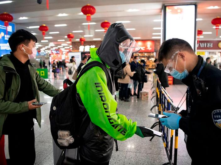 A passenger shows a green QR code on his phone proving his health status to security upon arrival at Wenzhou railway station on February 28, 2020.