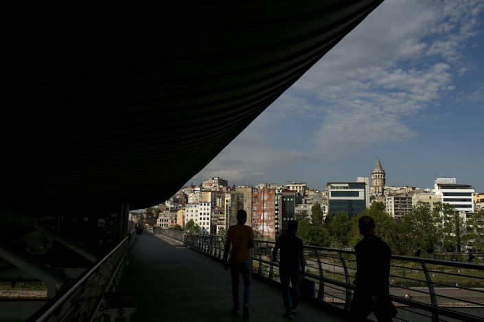 People walk on an underpass of the Galata Bridge over the Golden Horn in Istanbul, Friday, May 14, 2021.Turkey is in the final days of a full coronavirus lockdown and the government has ordered people to stay home and businesses to close amid a huge surge in new daily infections. But millions of workers are exempt and so are foreign tourists. Turkey is courting international tourists during an economic downturn and needs the foreign currencies that tourism brings to help the economy as the Turkish lira continues to sink. (AP Photo/Emrah Gurel)