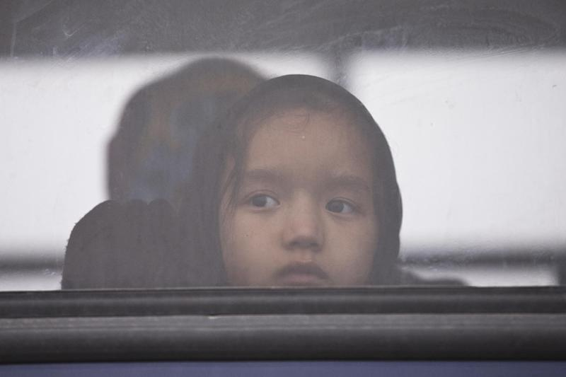 FILE - In this March 22, 2016 file picture a child looks out of the window of a bus before she and other migrants and refugees are taken to Moria camp, after they were rescued by a Norwegian Frontex patrol vessel off the coast of the Greek island of Lesbos. The head of the European Union border control, agency Frontex, Fabrice Leggeri, said Saturday Dec. 17, 2016 that about 350,000 migrants arrived in the EU this year so far. (AP Photo/Petros Giannakouris)
