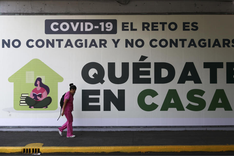 "FILE - In this Tuesday, March 31, 2020 file photo, a woman walks past a sign in Mexico City that translates in English to, ""COVID=19. The challenge is not to get it and not spread it. Stay home."" On Friday, May 22, 2020, The Associated Press reported on stories circulating online incorrectly asserting the letters in COVID-19 stand for certificate of vaccination identification and 19 stands for AI, artificial intelligence. COVID-19 stands for ""coronavirus disease 2019,"" according to the World Health Organization, which named it in February. In selecting a name, the WHO avoided anything that sounded similar to any geographical location, animal, individual or group of people, according to WHO director-general Tedros Adhanom Ghebreyesus. The name also had to be related to the disease and pronounceable. (AP Photo/Eduardo Verdugo)"