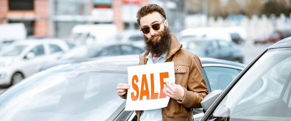 Stylish bearded salesman with sales plate near the cars on the open ground of a dealership