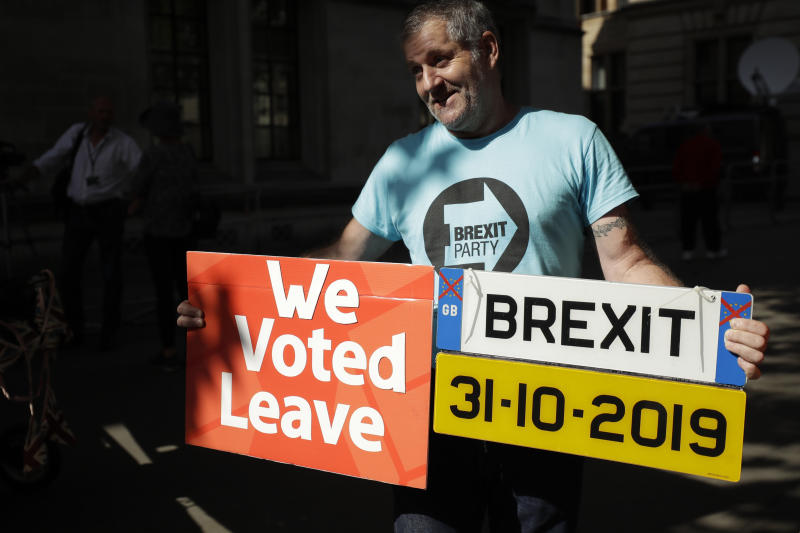 A Brexit supporter holds up a placard and a mock car number plate outside the Supreme Court in London, Thursday, Sept. 19, 2019. The Supreme Court is set to decide whether Prime Minister Boris Johnson broke the law when he suspended Parliament on Sept. 9, sending lawmakers home until Oct. 14 — just over two weeks before the U.K. is due to leave the European Union. (AP Photo/Matt Dunham)
