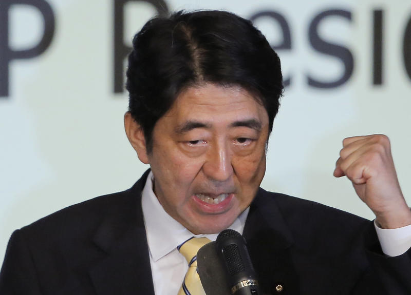 Former Prime Minister Shinzo Abe clenches his fist after winning the party leader election of Japan's Liberal Democratic Party in Tokyo, Wednesday, Sept. 26, 2012. Abe, known as a hawk and nationalist, won the election Wednesday to become president of the main opposition Liberal Democratic Party. (AP Photo/Itsuo Inouye)