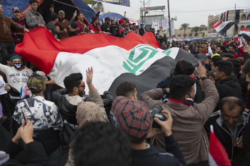 Anti government protesters carry a big Iraqi flag and chant anti Iran and anti U.S. slogans during the ongoing protests in Tahrir square, Baghdad, Iraq, Friday, Jan. 10, 2020. (AP Photo/Nasser Nasser)
