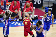 Atlanta Hawks' Trae Young, center, goes up for a shot between Philadelphia 76ers' Shake Milton, left, and Joel Embiid during the second half of Game 2 in a second-round NBA basketball playoff series, Tuesday, June 8, 2021, in Philadelphia. (AP Photo/Matt Slocum)