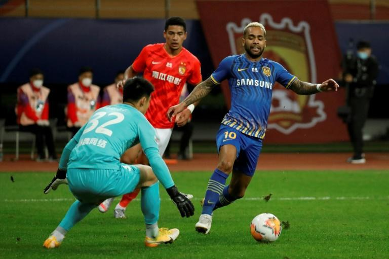 Jiangsu Suning's Alex Teixeira tries to beat the goalkeeper during the Chinese Super League football match against Guangzhou Evergrande in Suzhou
