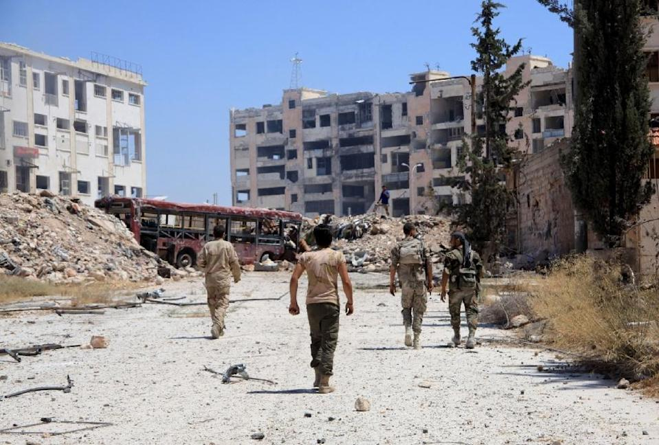 Syrian army soldiers patrol the area around the entrance of Bani Zeid after taking control of the previously rebel-held district of Leramun, on the northwest outskirts of Aleppo, on July 28, 2016 (AFP Photo/George Ourfalian)