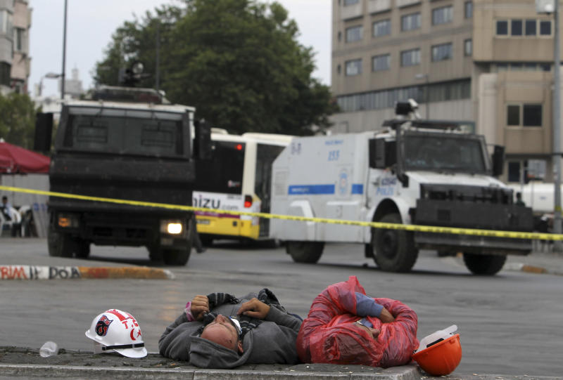 Protesters sleep on the marbles of Taksim Square near police water cannon trucks in Istanbul early Friday, June 14, 2013. A meeting between Turkey's Prime Minister Recep Tayyip Erogan and representatives of anti-government protesters ended early Friday without a clear resolution on how to end the occupation of a central Istanbul park that has become a flashpoint for the largest political crisis of his 10-year rule (AP Photo/Thanassis Stavrakis)