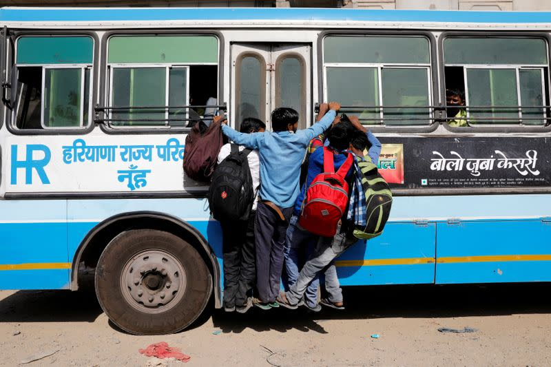 Migrant workers hang on to a door of their moving bus as they return to their villages, during a 21-day nationwide lockdown to limit the spreading of coronavirus disease (COVID-19), in Ghaziabad