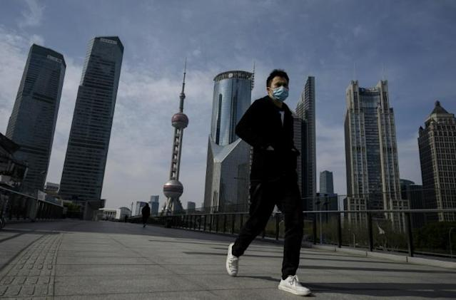 A man wearing a protective face mask walks on an overpass in Shanghai's Lujiazui financial district as officials announce the postponement of the April 19 Formula One Grand Prix (AFP Photo/NOEL CELIS)