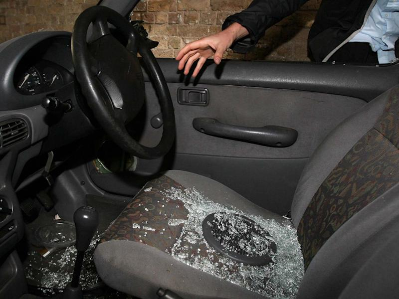 Undated file photo of a hand reaching into a car through a broken window: PA